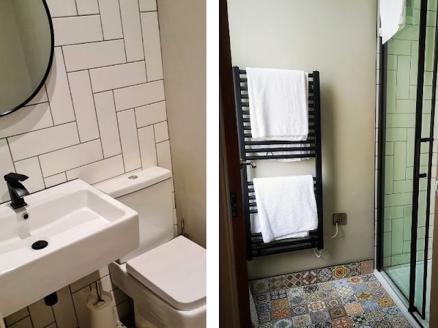 Two images side by side. The first is of the toilet room at Skippers Rest and shows a white toilet and sink with black taps, mirror and toilet roll holder. There is tiling on the walls that consists of white subway tiles with dark grout. The second image is of the shower area in Skippers Rest. It shows a large shower enclosure with modern black sliding shower door.  The inside of the shower enclosure is tiled in white subway tils with dark grout. There is a black industrial style vertical radiator/towel warmer that has two white towels on it. The floor is tiled in brightly coloured Moroccan style tiles.