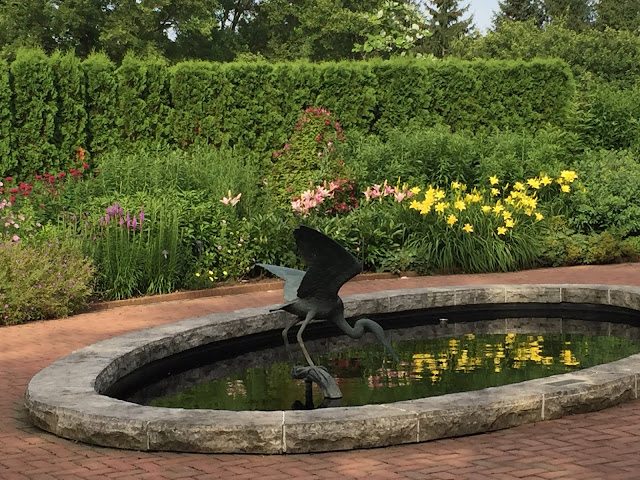 Enjoying a moment at the reflecting pond with a heron sculpture at Chicago Botanic Garden