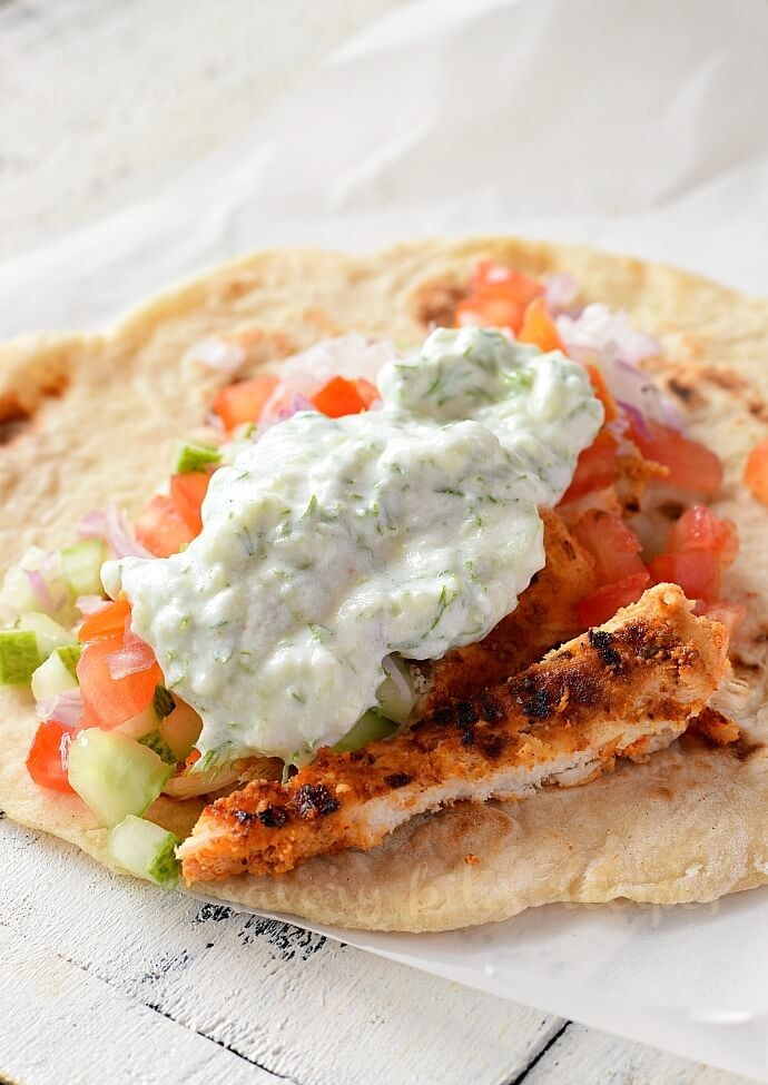 homemade pita bread topped with slaw,shredde chicken and tzatziki sauce