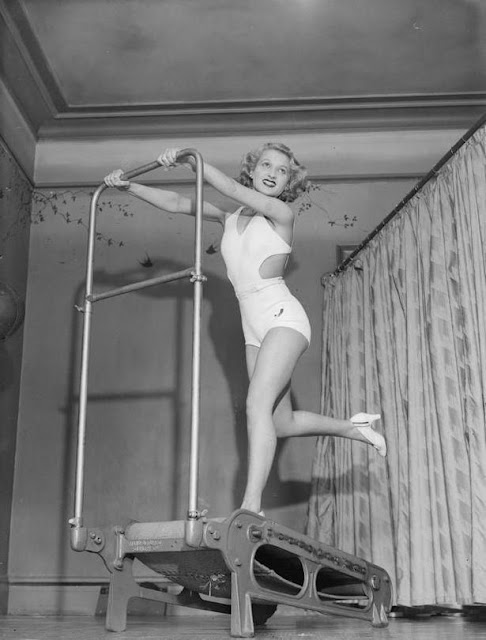 1934 photograph of exercising on a treadmill in lipstick and high heels