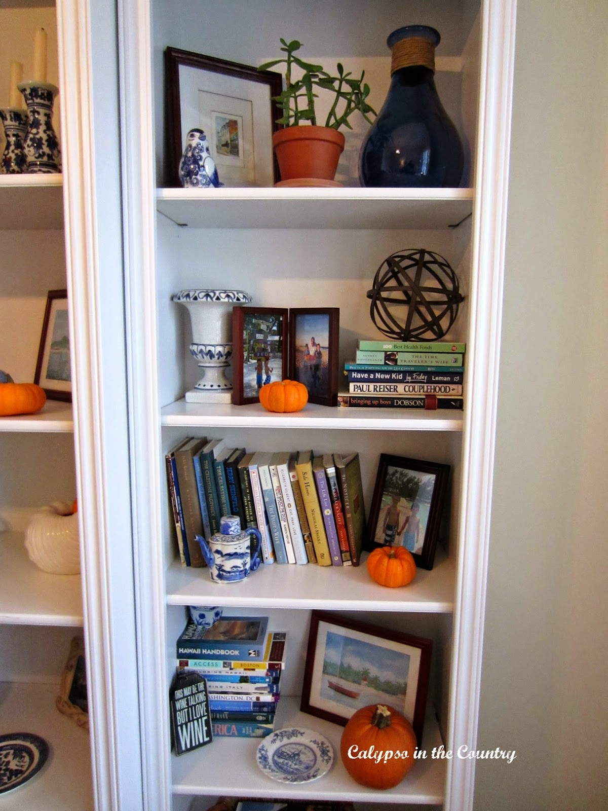 Fall Shelves in home office - using orange pumpkins to add to the blue and white decor