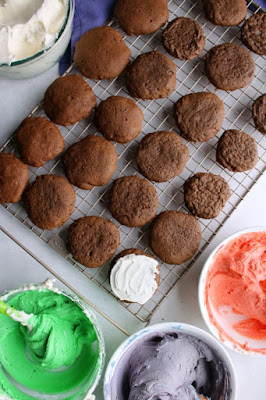 chocolate cookies on cooling rack with bowls of colored frosting
