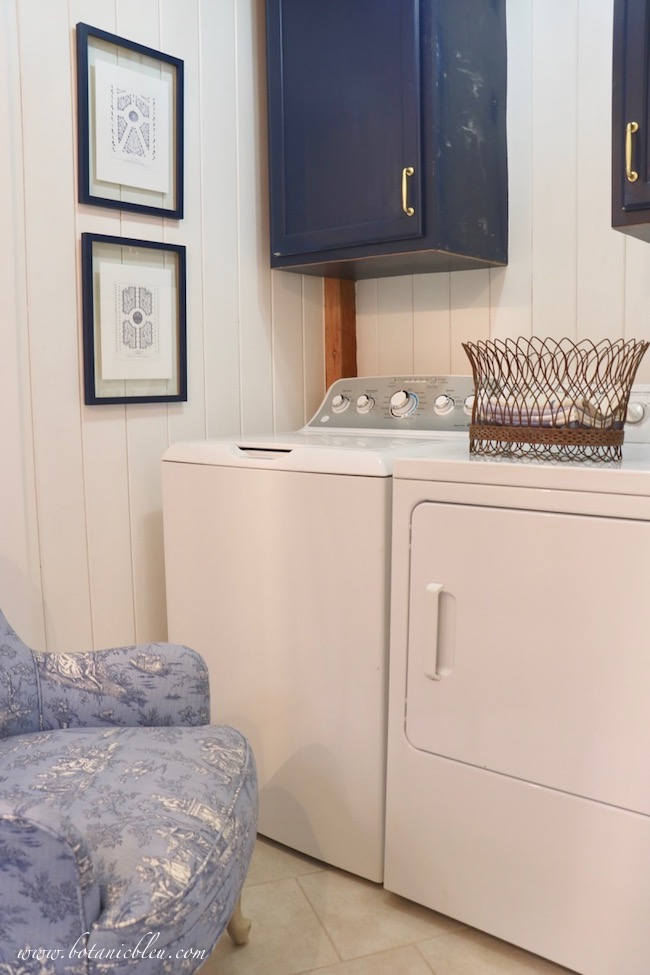 French Country laundry ORC French Style Details of French garden prints, toile upholstered chair, French wire basket with new navy cabinets in laundry room