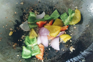 Sauteed onions capsicum red yellow bell peppers in a wok for chilli paneer recipe