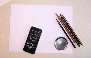 A picture of a phone with a compass app.