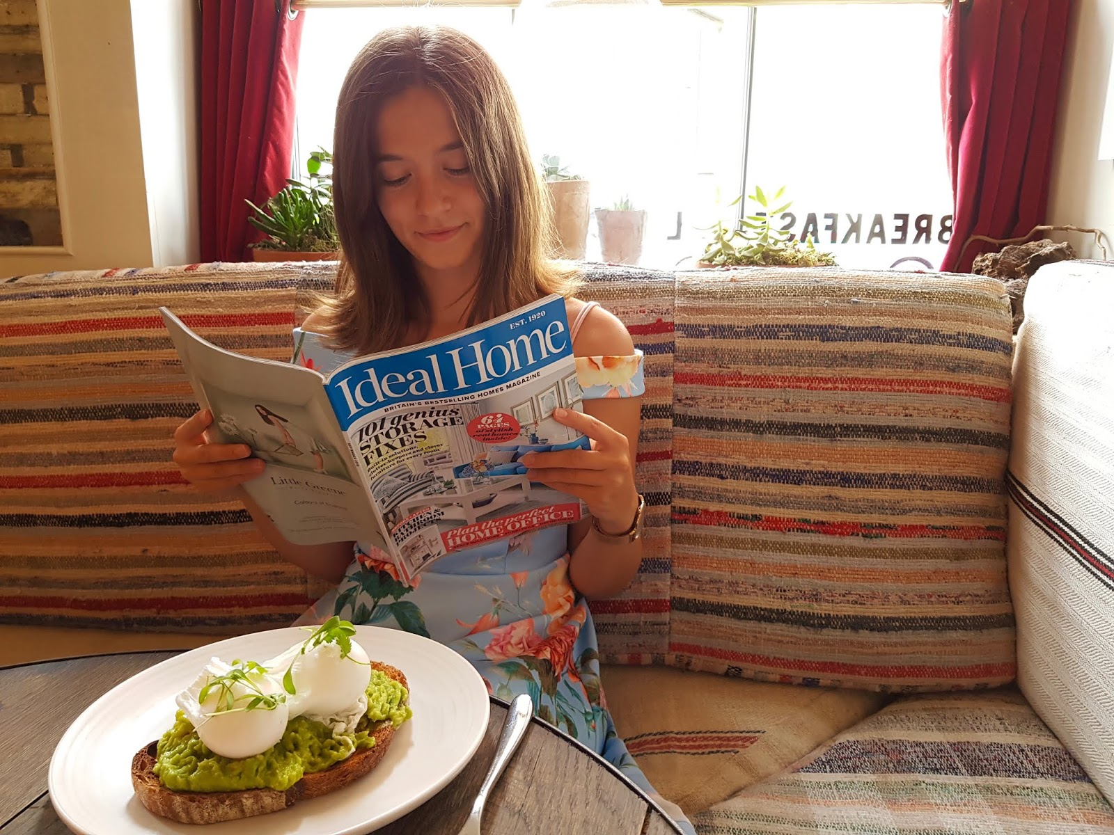 young woman reading property magazine with avocado on toast in front of her