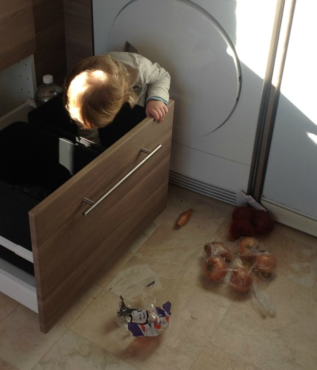Making Macaroni Cheese With A Toddler - Recipe. Toddler leaning into drawer and onions on the floor