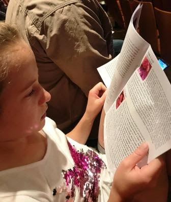 Girl looking at Beauty and the Beast JR programme at Peoples Theatre