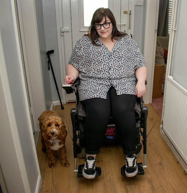 Woman in powerchair wearing heart print shirt, black jeans and trainers, next to her on wooden flooring is a red and white cockapoo