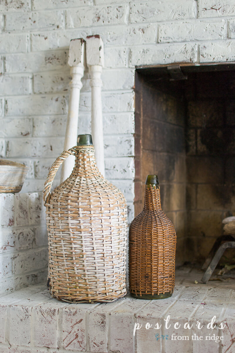 vintage wicker demijohns on white painted brick hearth