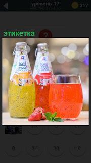 На столе стоят несколько бутылок с этикетками и стакан сока