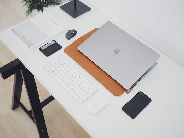White desk with Macbook laptop and keyboard and other stationary items on it.