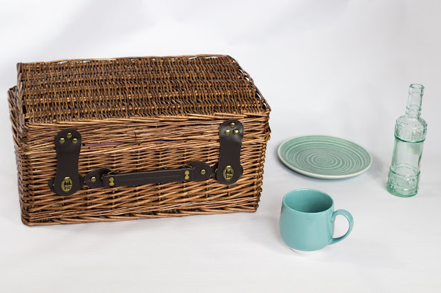 A hamper, mug, glass bottle and plate