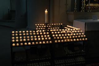 Viele Opferkerzen stehen im Altenberger Dom auf dem Kerzengestell. In der Mitte steht eine große Kerze.