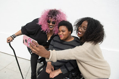 ID: three Black and disabled friends (a non-binary person with a cane and tangle stim toy, a non-binary person sitting in a power wheelchair, and an invisibly disabled woman) smiling and taking a cell phone selfie together. All are outdoors in front of a white wall.