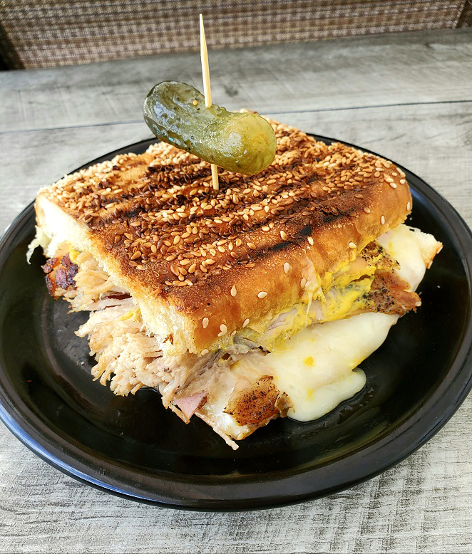 this is cuban sandwich with roasted pork, ham, cheese, mustard on a black dish and pickle on top