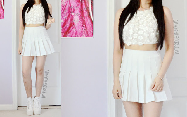 An all-white summer festival outfit featuring the white mesh floral applique embroidered halterneck crop top from Dresslink (a dupe of the For Love and Lemons Secret Garden bra), worn with an American Apparel style white pleated tennis skirt.