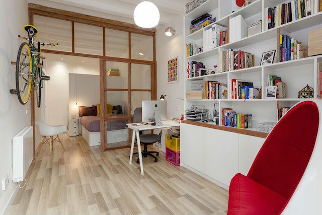 despacho con librería conectado con el dormitorio a través de puertas correderas de cristal y madera