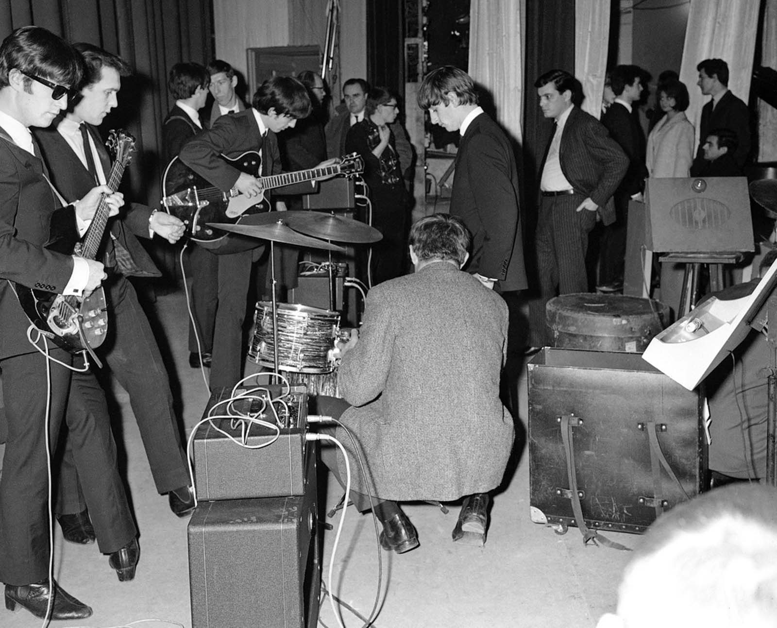 John Lennon, left; George Harrison, center holding guitar; and Ringo Starr from the Beatles, backstage in Versailles, France, on January 15, 1964.