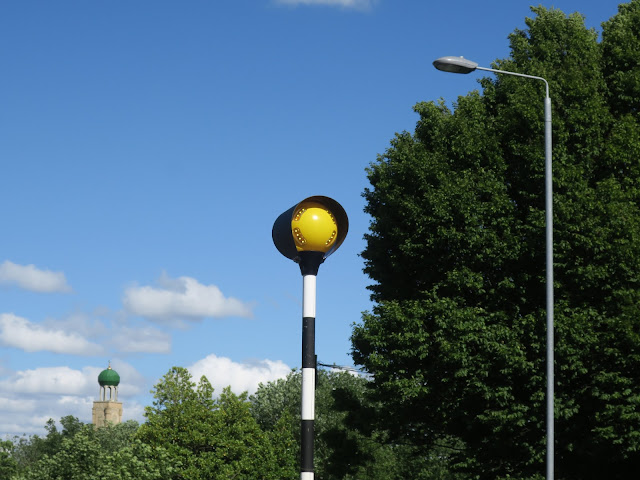Top of mosque, yellow light for pedestrian crossing and lampost.