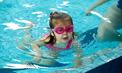 image of a child happy child swimming in the pool. Avoid Child Drownings. Take Responsibility Around Water.