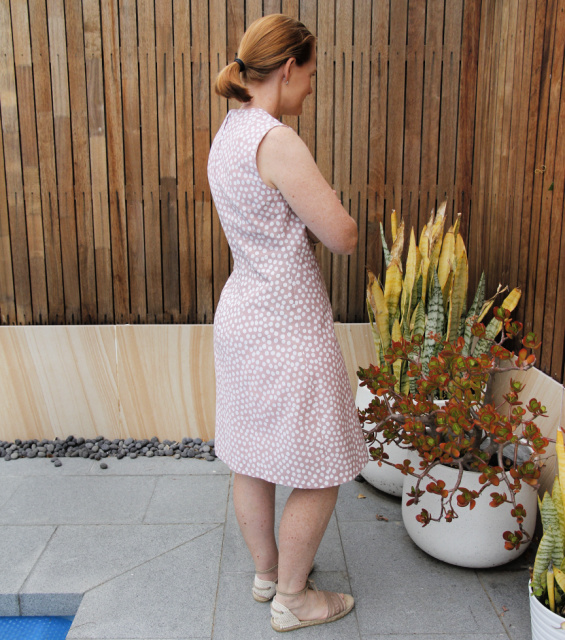 a woman posing in a pink polka dot dress with her back towards the camera