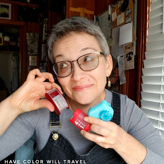 A closeup of a woman in her 40's with short hair holding three colorful pencil sharpeners. She is happy and curious.