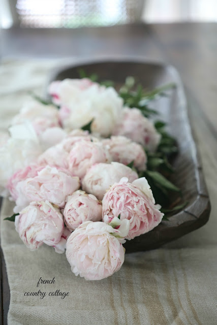dough bowl on table with peonies and grainsack