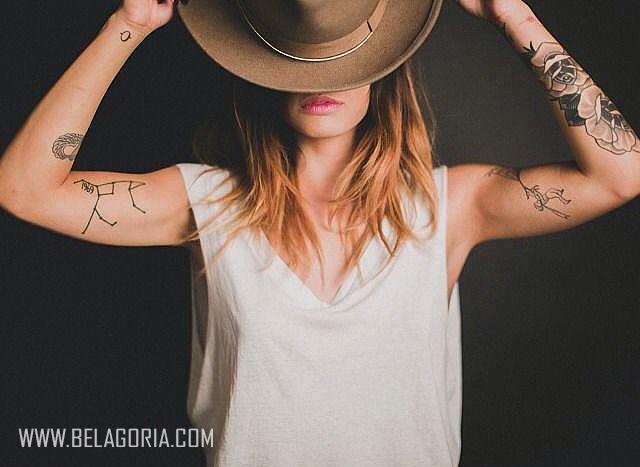 Chica con sombrero vaquero se lo quita y vemos en sus brazos tatuajes de constelaciones