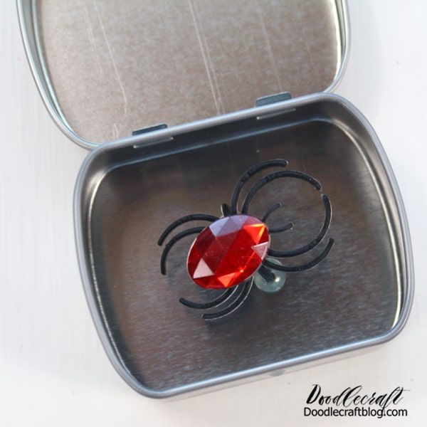 Make the perfect trick for Halloween with this little surprise spider mint tin! This cute little tin is the equivalent of telling someone there's a spider in their hair! I made this and stuck it on my refrigerator and guess what!? It tricked all three of my teenagers!