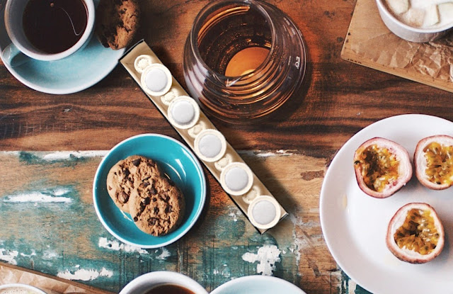 The image shows the compostable coffee pods sitting on a rustic wooden table. The pods are surrounded by breakfast items such as breakfast biscuits, coffee cups, honey jars and fruit.