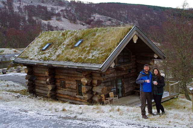 Couple standing in front of Eagle Brae Log Cabin in Scotland