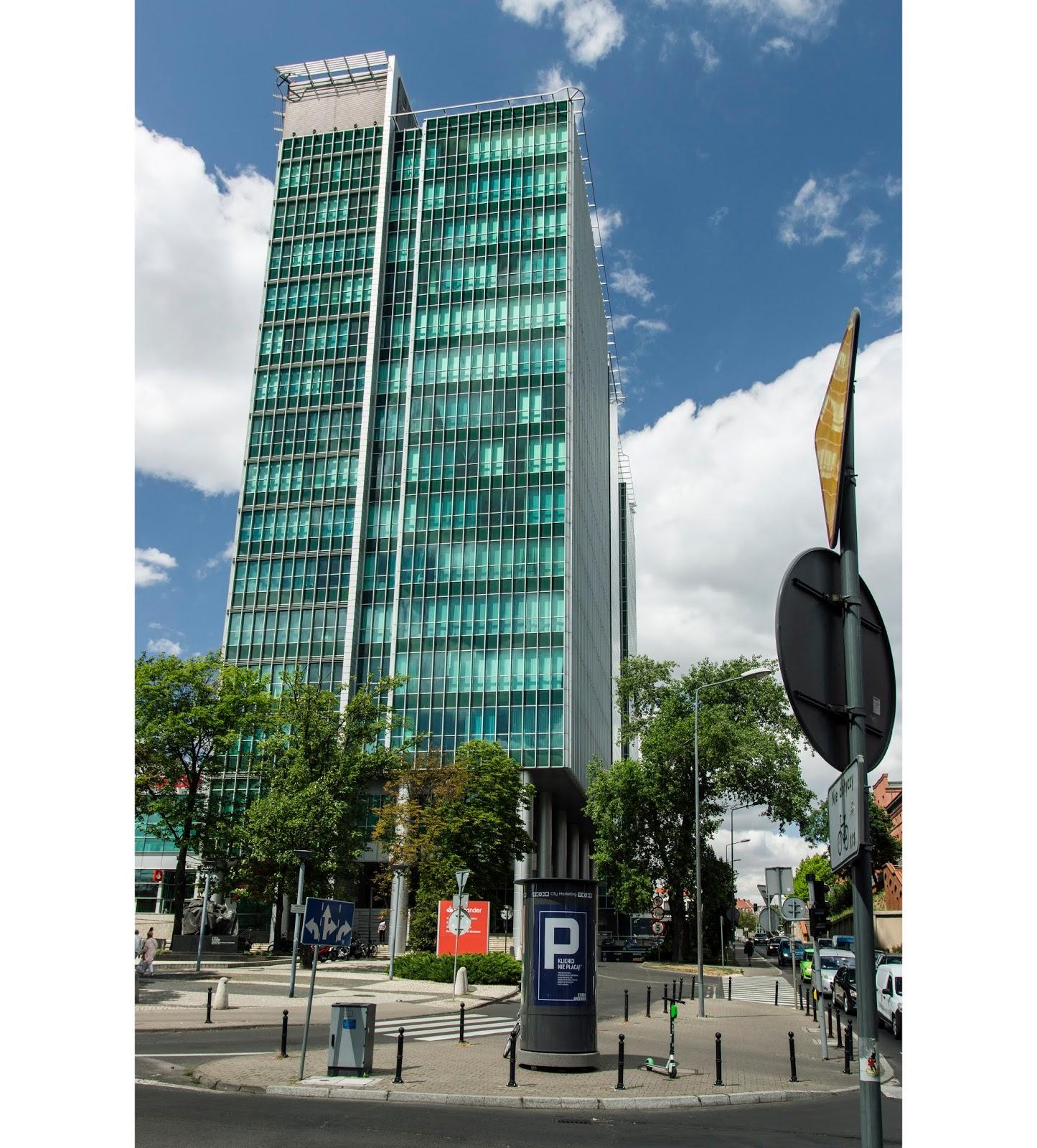 Szklana fasada budynku Financial Centre. Mieniąca się w słońcu na niebiesko tafla szkła z elementami stalowymi. Dominujące pociągłe pionowe linie. Na pierwszym planie słup ogłoszeniowy.