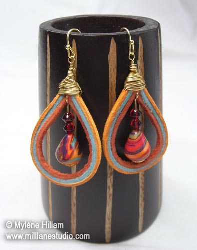 Lengths of rust, aqua and orange peel suede lace fashioned into a teardrop earring, surrounding a marbled red, turquoise and orange teardrop bead.