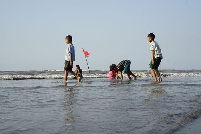 Anak-anak riang bermain air laut