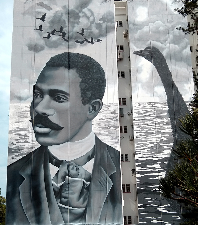 A portrait in a wall of a black man in black and with aside a swan.