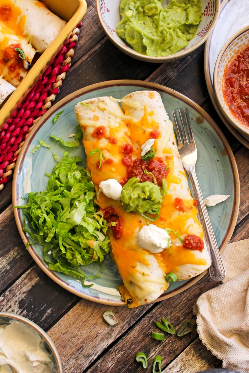 Top view of two burritos on a blue plate topped with a spoonful of greek yogurt, salsa, and guacamole on top with a side of shredded lettuce.  Plate is on a dark wood background.