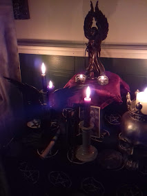An altar with several tall black dinner candles in grey ceramic holders. The base altar cloth is black with white pentacles. On the left side of the altar is a statue of the Goddess Badb with black out-stretched wings and black robes. Beside the statue of Badb there is a black stone dish of white salt with a raised pentagram in the dish. At the front of the altar is a wand carved roughly from oak. On the left side of the altar is a large, life-size resin skull with a crown, being used as a candle-holder for melting white candle. In the center of the altar there is a wooden stand with a blood-red damask brocade cloth on it; on the stand is a bronze-effect resin statue of the Morrigan with great wings rising up behind her, and at the feet of the statue there are two pewter Celtic knotwork/insular interlace design candle-holders for tealights, a pair of lit tea-lights are in them casting a soft glow across the statue. At the base of the stand is a greetings card for Samhain with red and black artwork depicting crows and the Morrigan. The altar is infront of a white wall with green paneling with white dado-rail. On the wall are a plaque of the Green Man and a female equivalent 'green woman' as a wall-pocket. The image is candle-lit. At the very left edge of the image a green candle is visible