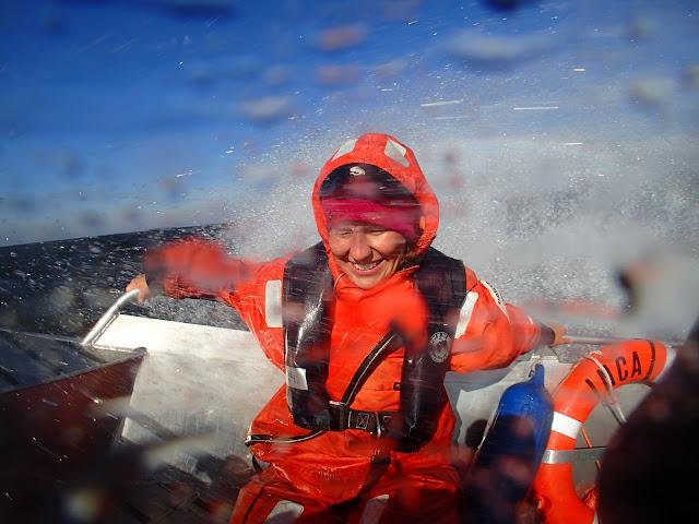 Henkilö istuu aaltojen pärskeissä veneen keulassa ja hymyilee
