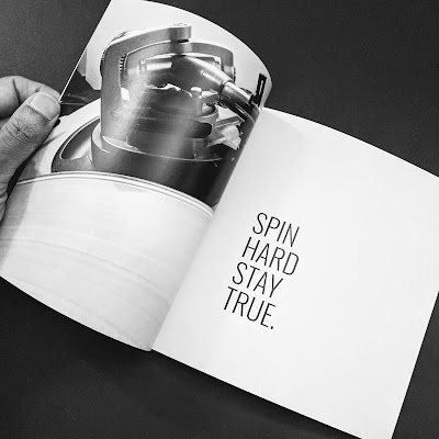 "The DJ room photo-book by Ryan Cornelius opened to a page with a photo of a turntable and saying, ""Spin hard, stay true."""