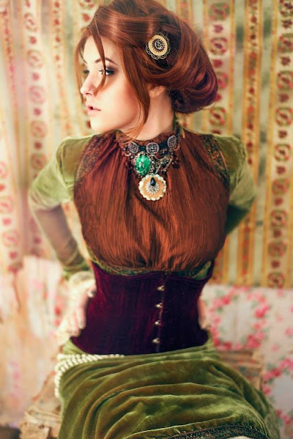 Woman wearing a green velvet Victorian dress as part of a Steampunk costume. Elegant Steampunk clothing.