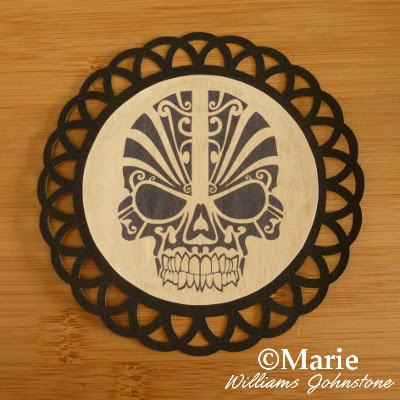 Black circle skull motif on a scallop edge black card frame