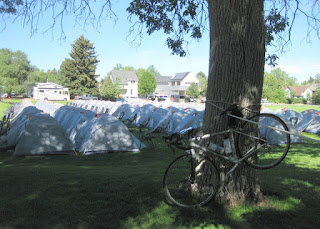 My bicycle parked in the bike corral, rows of gray sherpa tents beyond, Beall Park, Bozeman, Montana