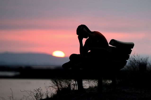A boy sitting on a bench near a coast when sunset is about to happen but his head is in one of his hands as a sign distress and depression.
