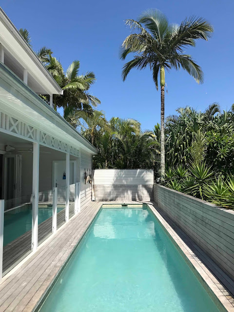 A swimming pool next to a white weatherboard house with palm trees in the background.