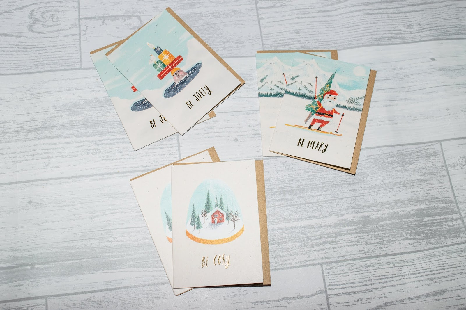 Three Christmas Card designs showing Santa on skis, a seal with presents on his head and snow covered house in a snow globe.