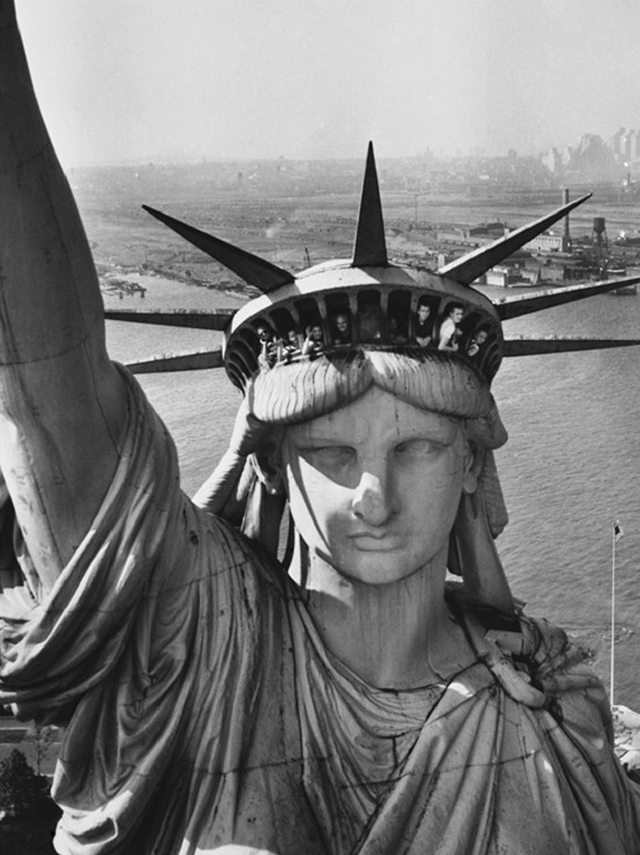 SIGHTSEERS HANGING OUT WINDOWS IN CROWN OF STATUE OF LIBERTY WITH NJ SHORE IN THE BACKGROUND