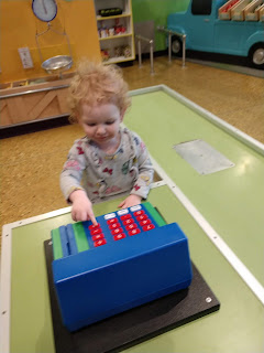 a toddler with curly strawberry blonde hair pushes buttons on a toy cash register at LaunchPad Children's Museum in Sioux City, Iowa