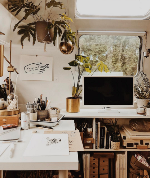 Bright bohemian white tv and working area of a vintage airstream with lots of plants