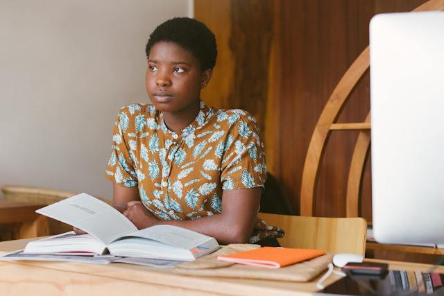 Mulher negra sentada no escritório refletindo